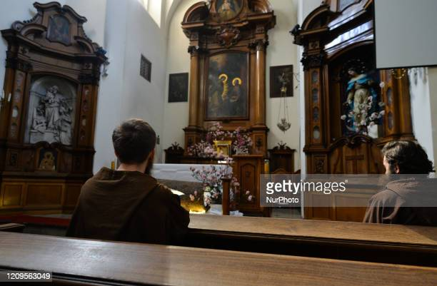 Two monks from the Order of Friars Minor Capuchins pray as they finished to prepare the tomb of Christ inside the Cloister Church in Krakow On...