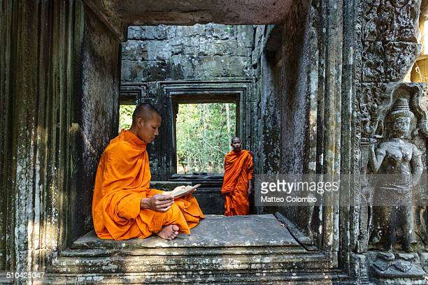 two monks inside the ruins of angkor, cambodia - traditionally cambodian stock pictures, royalty-free photos & images