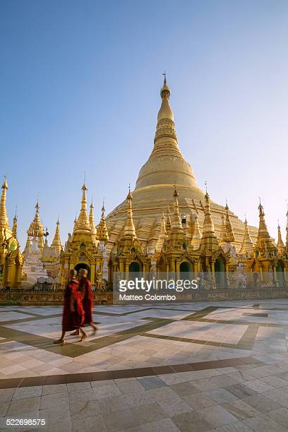 two monks walking near shwedagon paya, myanmar - yangon stock pictures, royalty-free photos & images