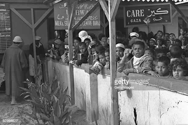 Two months after Israel's first occupation of this wartorn area Arabs line up for their milk rations at a United Nations distribution center January...
