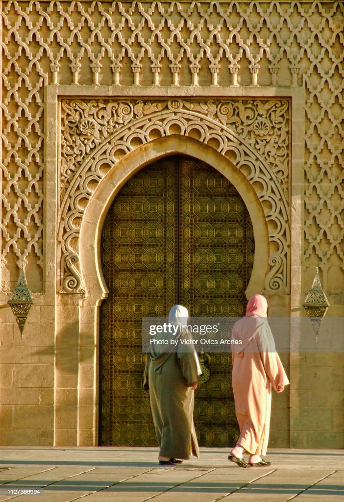 Two Moroccan Muslim women walking in front of the Mosque of the Mausoleum of Mohammed V in Rabat, Moroccom : Foto de stock