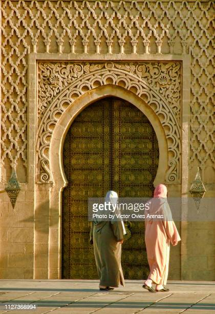 two moroccan muslim women walking in front of the mosque of the mausoleum of mohammed v in rabat, moroccom - victor ovies fotografías e imágenes de stock