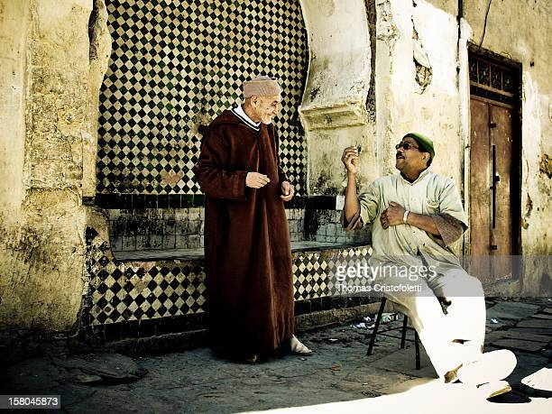 Two Moroccan people chatting outside the wall of the Medina of Fez .