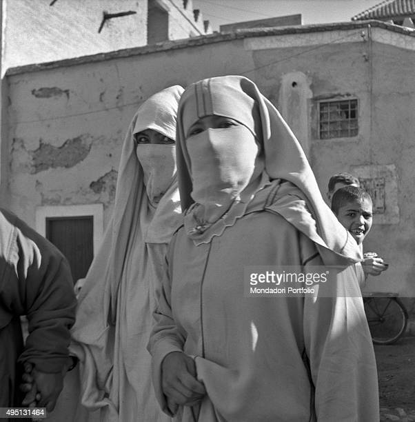 Two Moroccan women's eyes look at the camera they are dressed in the traditional clothes called djellabah and wear the veil that covers her faces in...