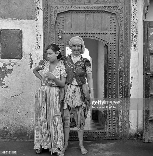 Two Moroccan young women in traditional clothes posing in front of a door in recent times in Morocco some women have started to assert themselves in...