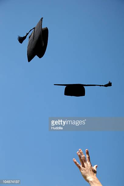 Two mortarboards being thrown