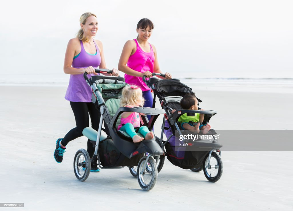 Two mothers and babies in strollers jogging on beach : Stock-Foto