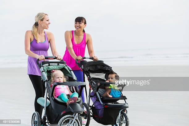 2 つの母親と赤ちゃん用ベビーカーでビーチを歩く