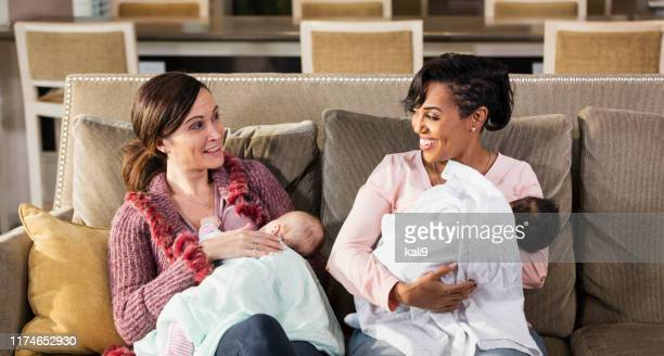 two mothers and babies on sofa, nursing - breastfeeding stock pictures, royalty-free photos & images