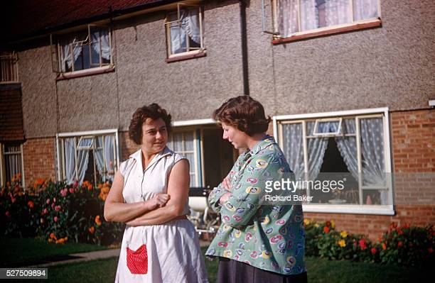 Two mothers and neighbours gossip with arms folded outside their houses on an Essex estate in the early nineteen sixties Wearing aprons popular for...