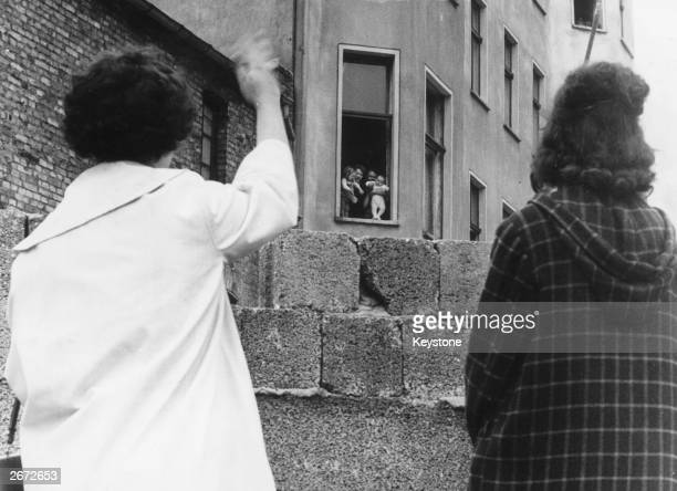 Two mothers can only wave to their children and grandchildren in the Soviet sector of Berlin from across the Berlin wall