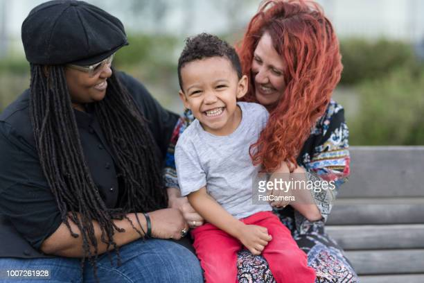 two mothers holding their son on their laps outside at the park - gay person stock pictures, royalty-free photos & images