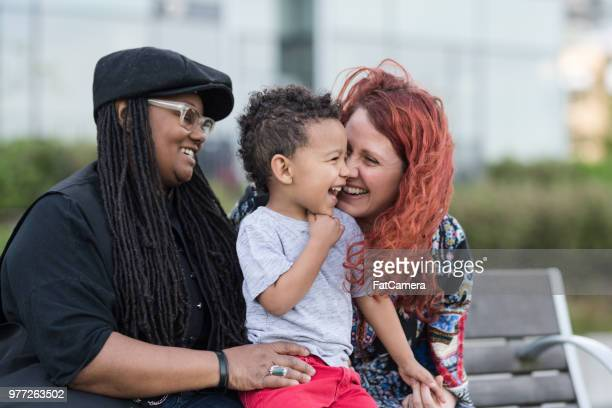 two mothers holding their son on their laps outside at the park - lesbica imagens e fotografias de stock