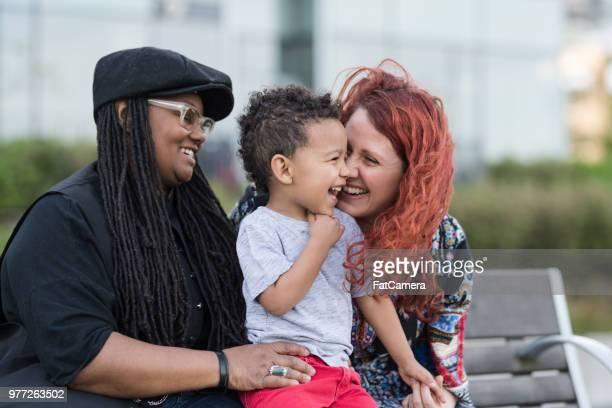 twee moeders houden van hun zoon op hun rondjes buiten in het park - adoptie stockfoto's en -beelden