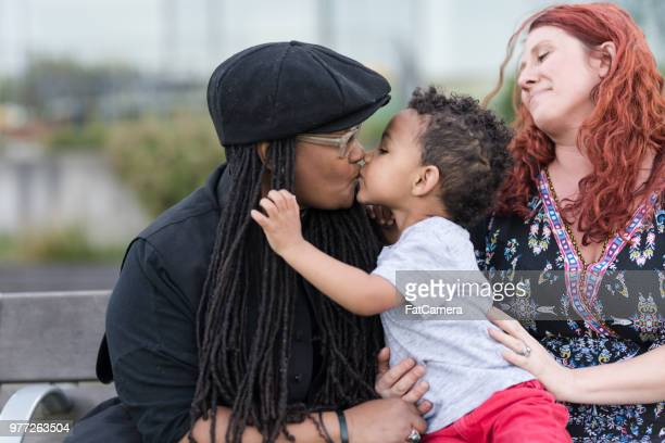 Two mothers holding their son on their laps outside at the park