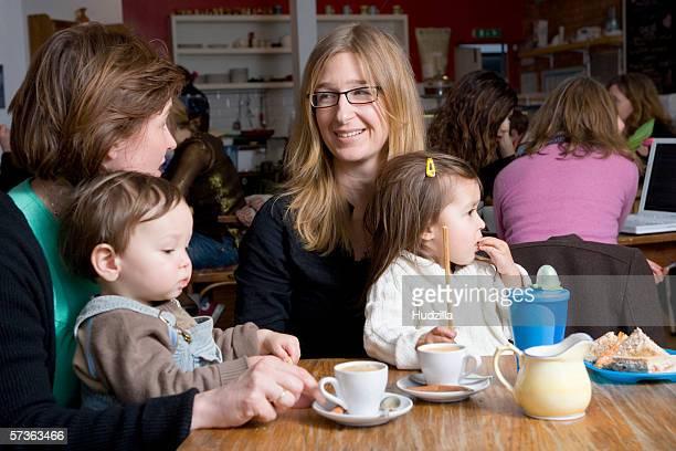 Two mother's in a cafe with children sitting on their laps