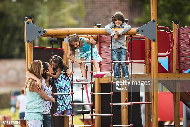 Two mothers spending a day with their kids at playground.