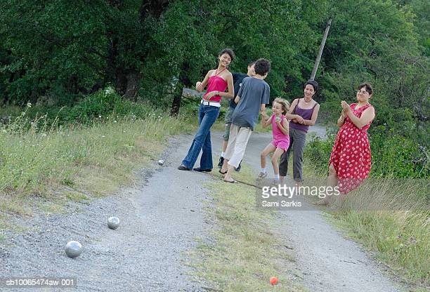 Two mothers with four children (7-14) playing french boules game on dirt road