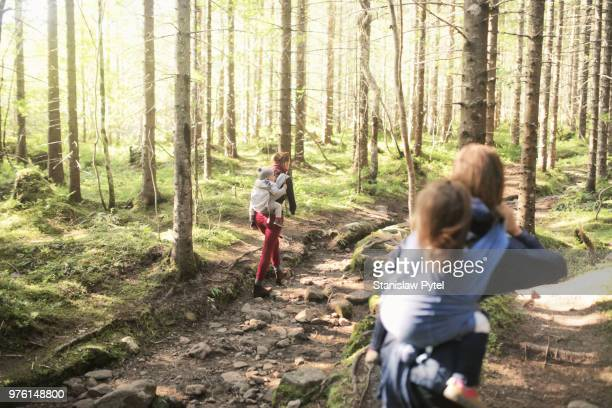 Two mothers with kids in baby carriers walking in forest