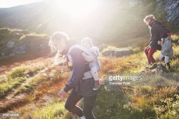 Two mothers with kids trekking in mountains at sunset