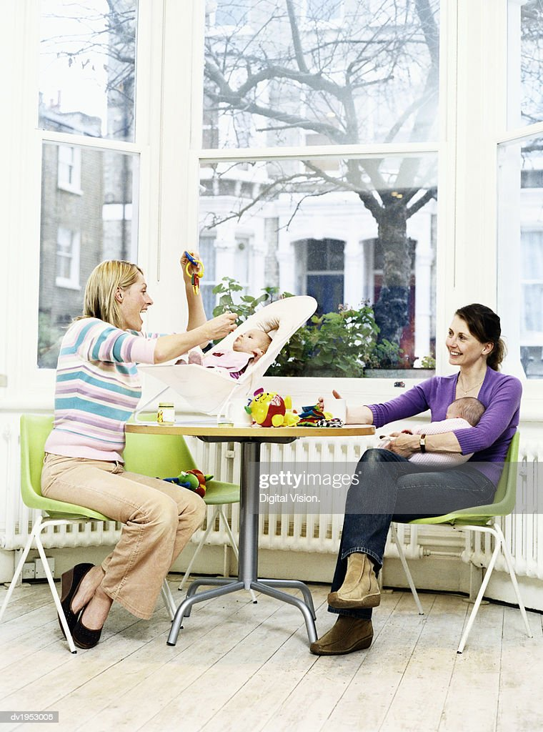 Two Mothers With Their Offspring Sitting at a Table : Stock Photo