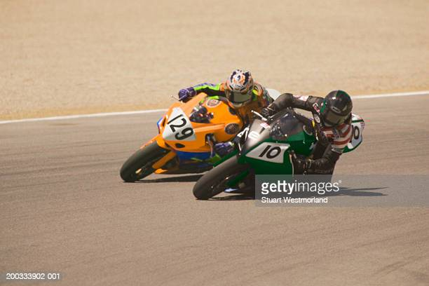 two motorcycle racers taking curve on track (digital enhancement) - motorcycle racing stock pictures, royalty-free photos & images