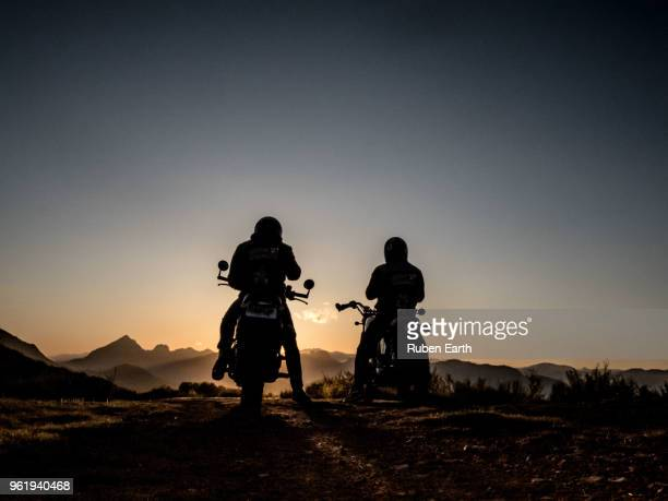Two motorcycles and riders looking at the mountains