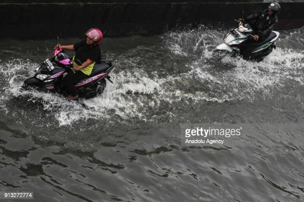 Two motorcycles wade through flood caused by the rising of sea level in SemarangDemak highway in Central Java Indonesia on February 2 2018 Local...