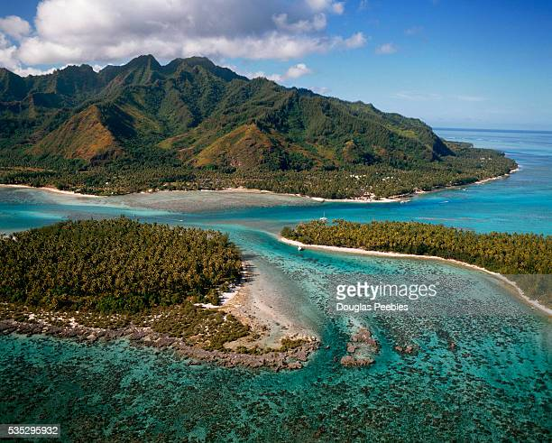 Two motus, small islets on a coral atoll, off the coast of Moorea, in the Society Islands of French Polynesia.