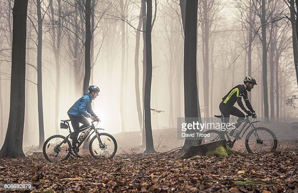 two mountain bikers in misty forest - mountain bike stock pictures, royalty-free photos & images