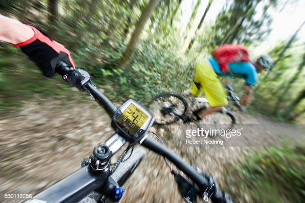 two mountainbikers racing down mountain track - メートル ストックフォトと画像
