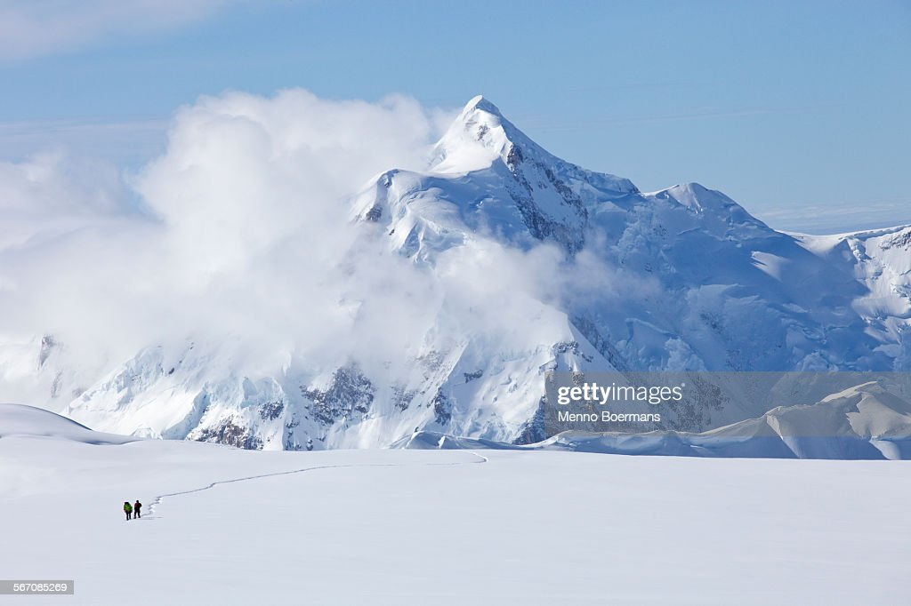 Two mountaineers are crossing a glacier on Mt. McKinley, Alaska. Mount Hunter is in the background. : Stock Photo