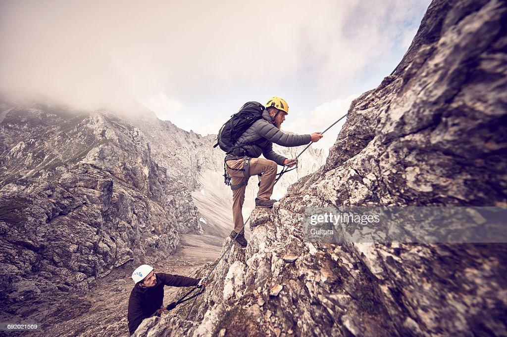 Klettersteig Innsbruck Umgebung : Two mountaineers climbing mountain via ferrata klettersteig