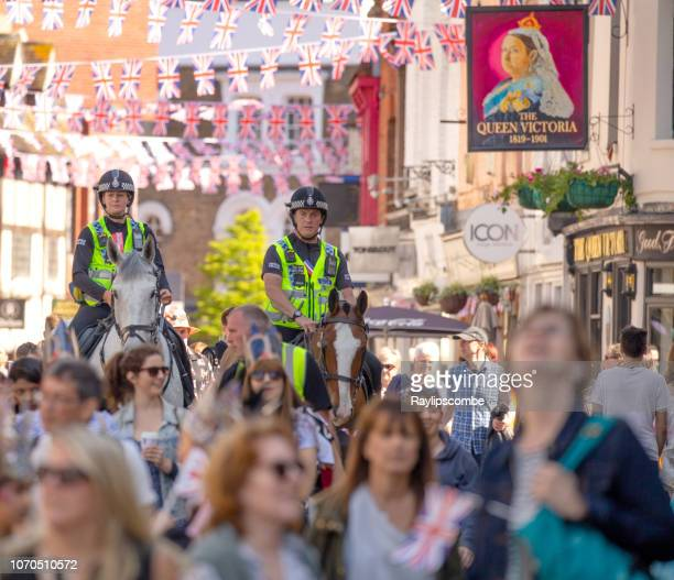 two mounted police officers marshalling the crowds of people on their way to celebrate the marriage of meghan markle and prince harry at st george's chapel at windsor castle - meghan stock photos and pictures