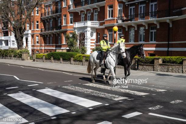 Two mounted police officers ride their horses across the iconic Abbey Road crossing as a Highways Maintenance team take advantage of the COVID19...