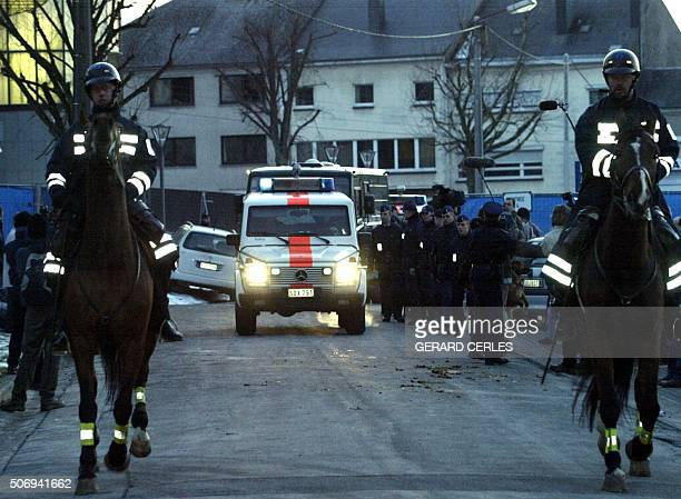 Two mountedhorse policemen escort the policevan carrying Belgian convicted paedophile Marc Dutroux as it leaves the Arlon courthouse 02 March 2004...