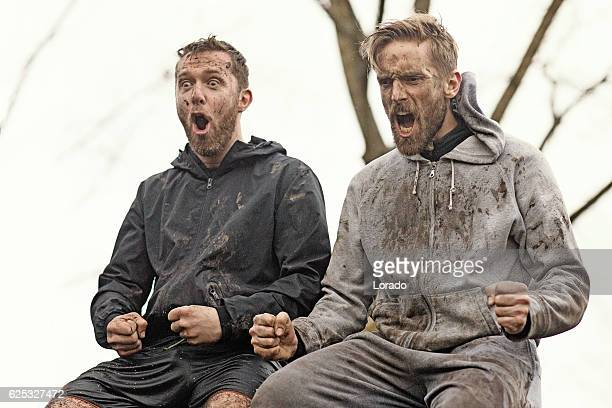 Two mud run teammates yelling sitting together on wall obstacle