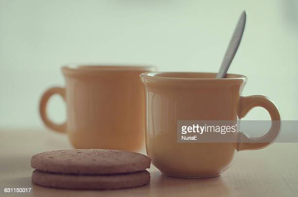 Two mugs of tea with biscuits
