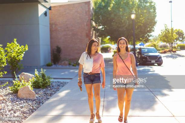 two multi generational females walking on city street together - eyecrave  stock pictures, royalty-free photos & images