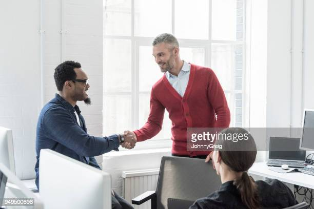 Two multi racial businessmen shaking hands in office with young man in foreground