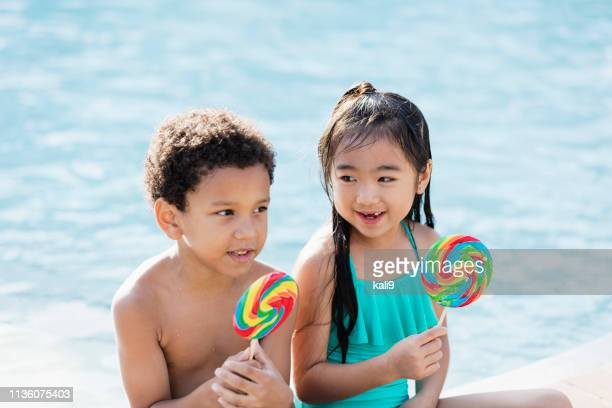 Two multi-ethnic children sitting by pool with lollipops