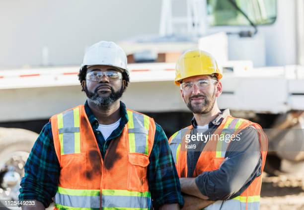 two multi-ethnic construction workers - construction worker stock pictures, royalty-free photos & images