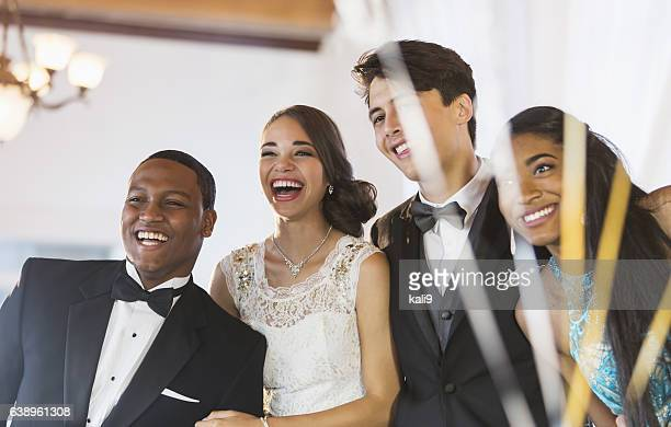 Two multi-ethnic couples in tuxedos and dresses