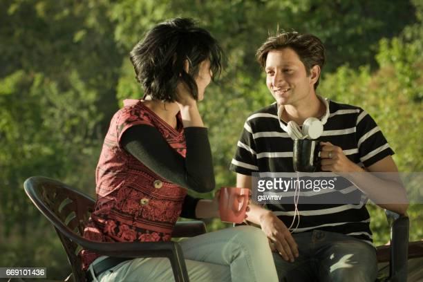 Two multiethnic happy friends enjoying gossip with coffee.