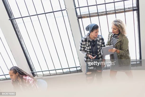Two multi-ethnic stylish women discussing digital tablet