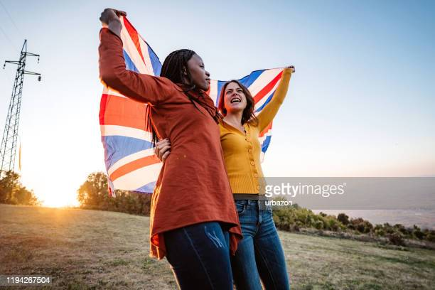 two multi-ethnic women holding british flag - union jack stock pictures, royalty-free photos & images