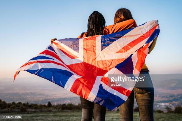 two multi-ethnic women holding british flag - african american culture stock pictures, royalty-free photos & images