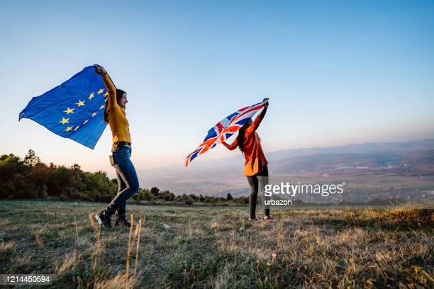 deux femmes multiethniques retenant l'union européenne et le drapeau britannique - brexit photos et images de collection