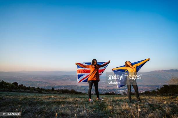 two multi-ethnic women holding european union and british flag - brexit stock pictures, royalty-free photos & images