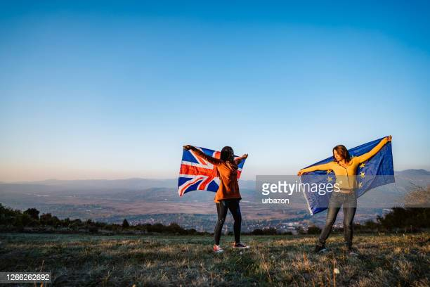 two multi-ethnic women holding european union and british flag - african american culture stock pictures, royalty-free photos & images